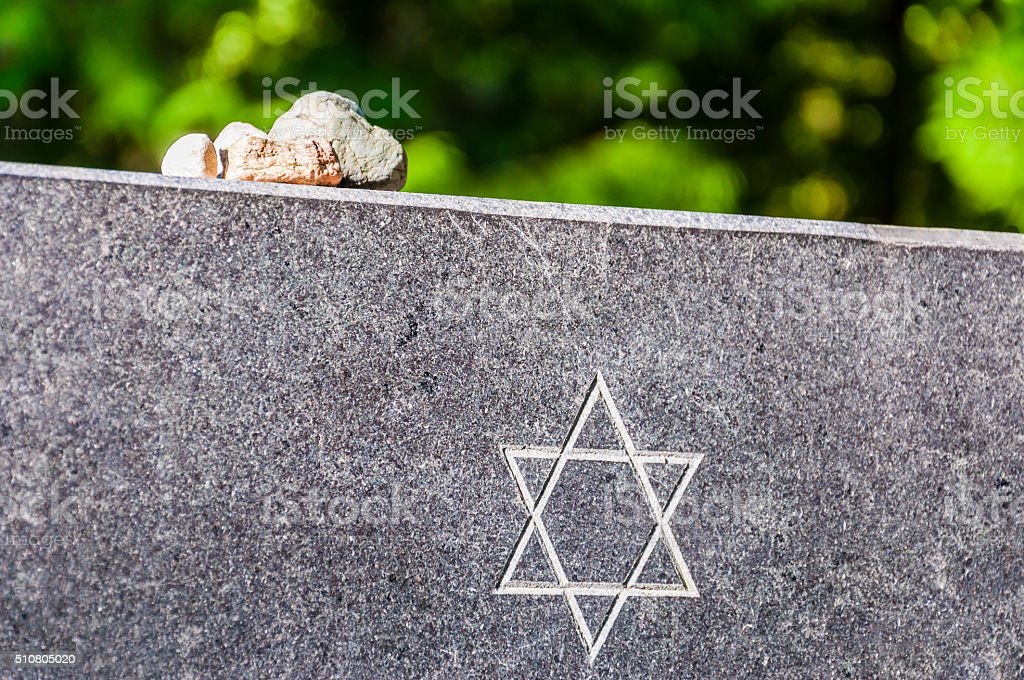 Stones on Jewish Memorial granite plate with Star of David. stock photo