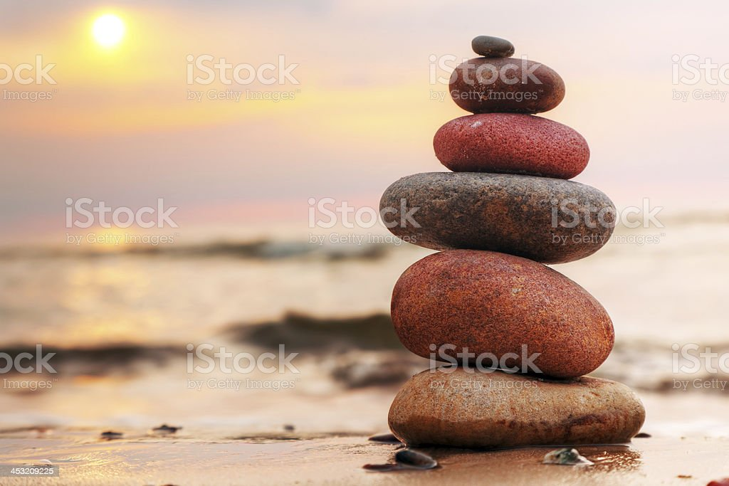 Stones pyramid on sand symbolizing zen, harmony, balance stock photo