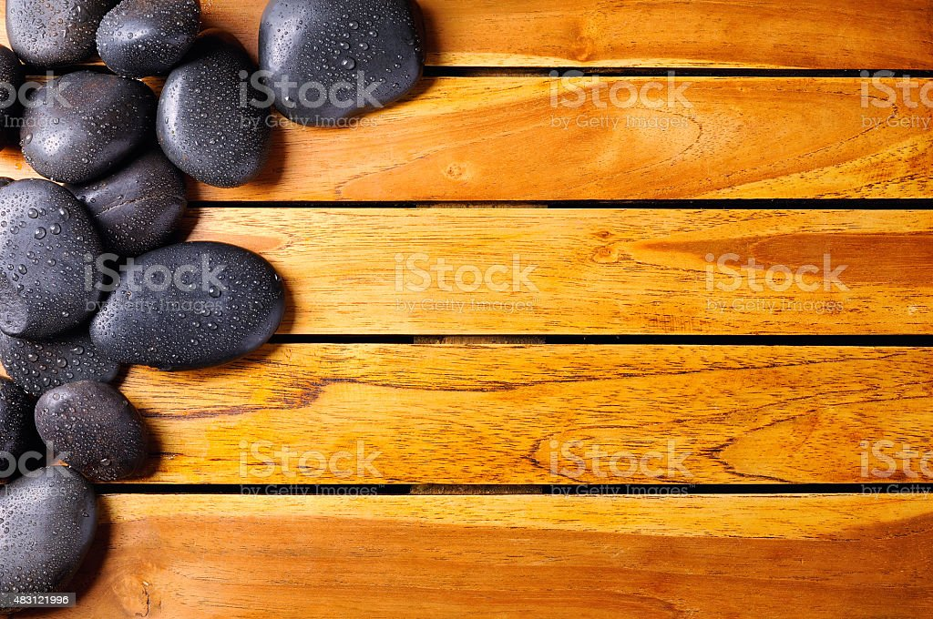 Stones with drops in the top left corner on wooden stock photo