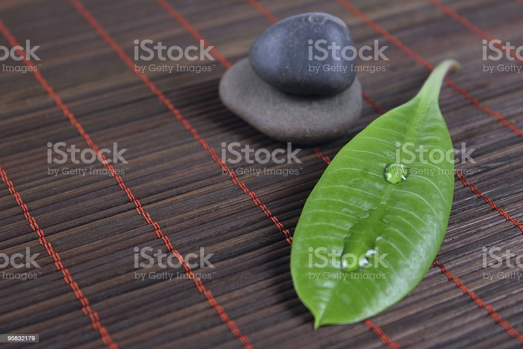 Stones with green sheet on a bamboo napkin royalty-free stock photo