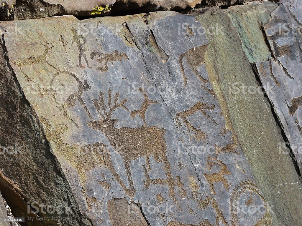 Stones with of people and animals petroglyphs stock photo