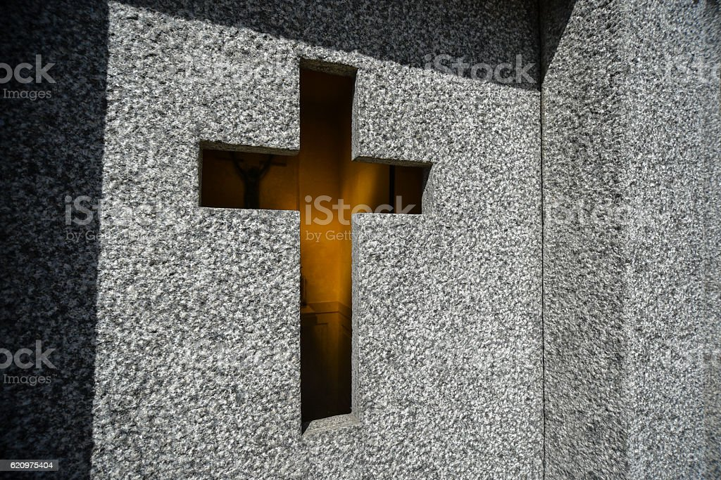 Stonewall with a cross of a tomb stock photo