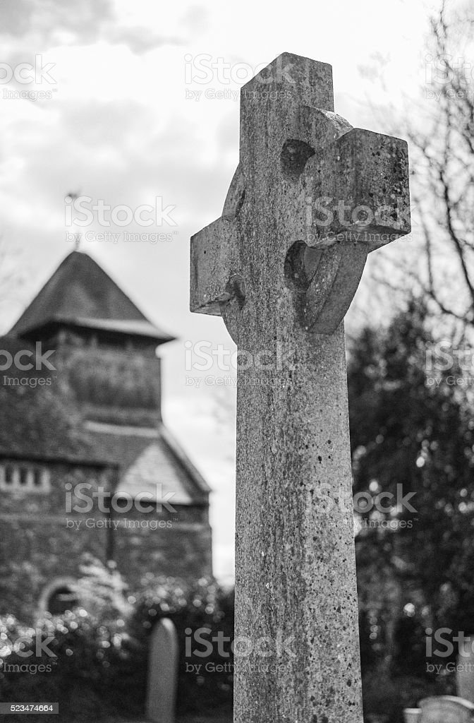 Stonework cross standing tall in front of its church stock photo