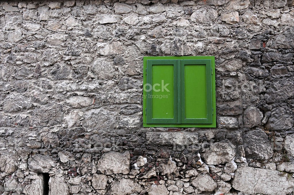 stony house wall with a closed green window royalty-free stock photo