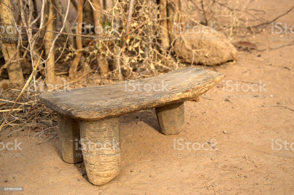 stool with three legs in an african court yard stock photo