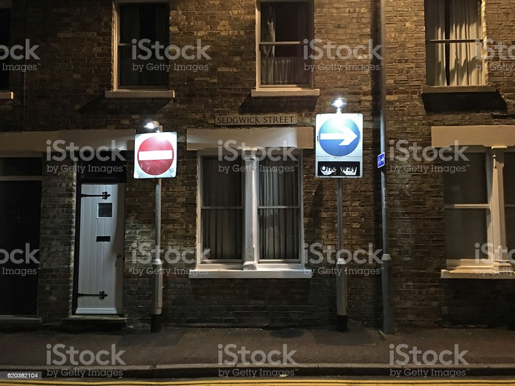 Stop and One Way street sign at night stock photo