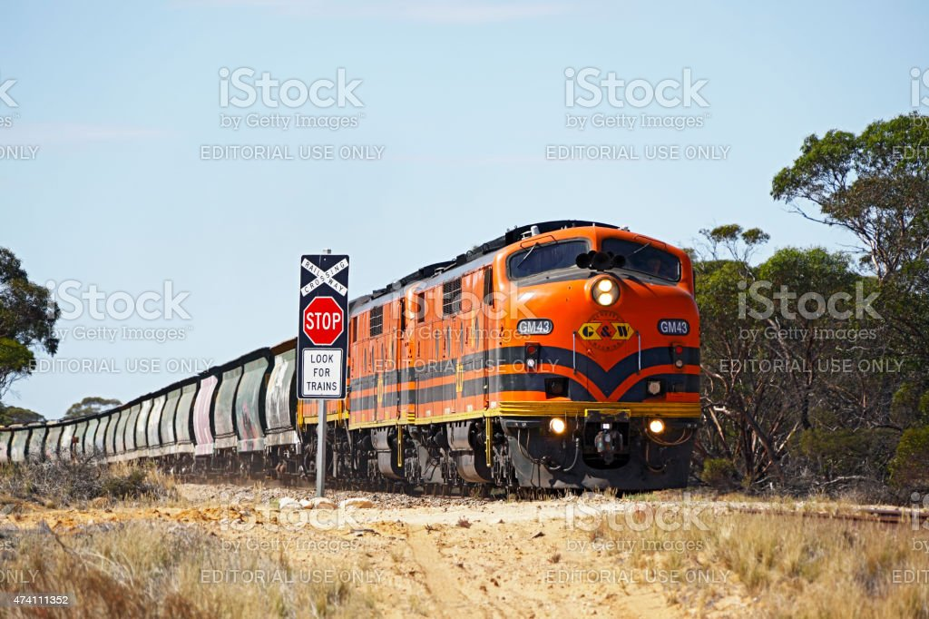 Stop for Trains: Vintage locomotives, grain train passing rural crossing stock photo