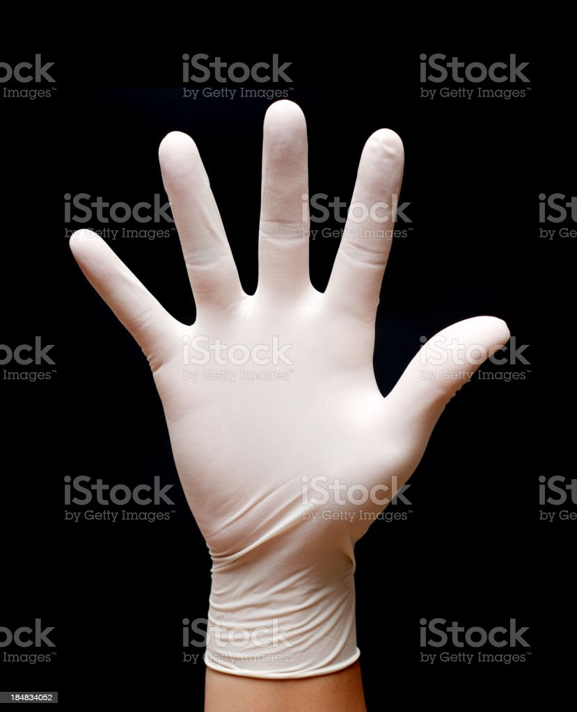Stop! Man's hand wearing protective gloves isolated on black background stock photo