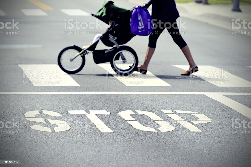 Stop painted on street, mother with baby stroller stock photo