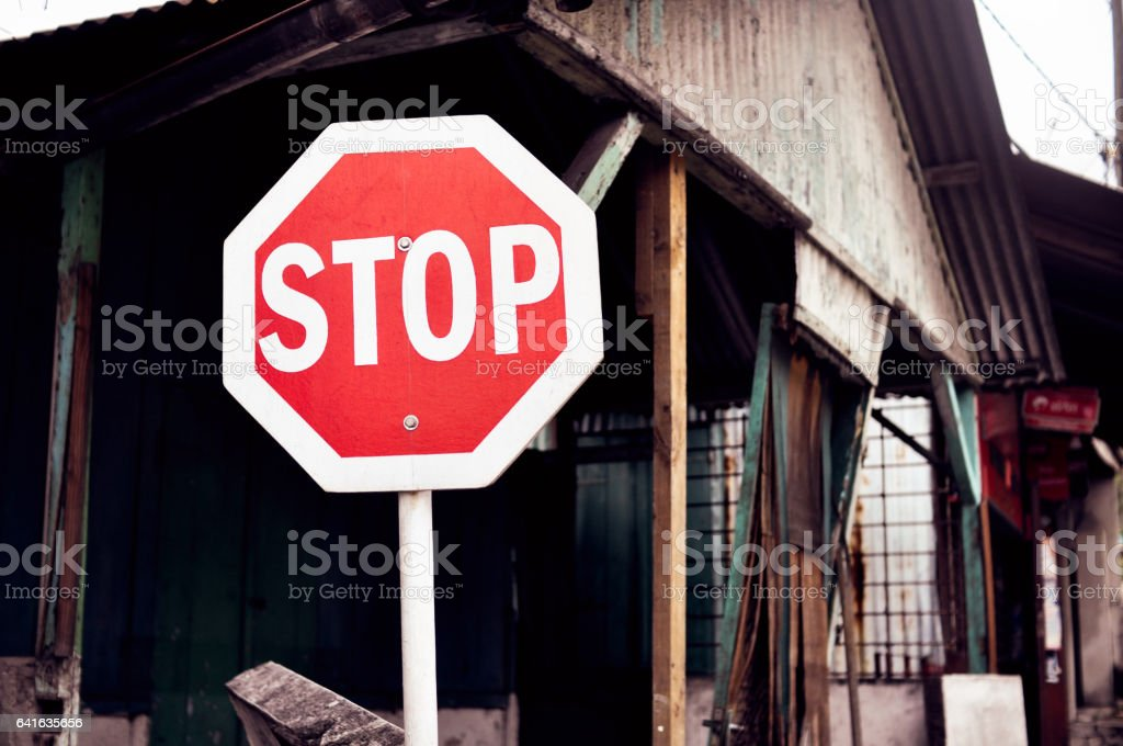 Stop sign against the backdrop of dilapidated housing stock photo