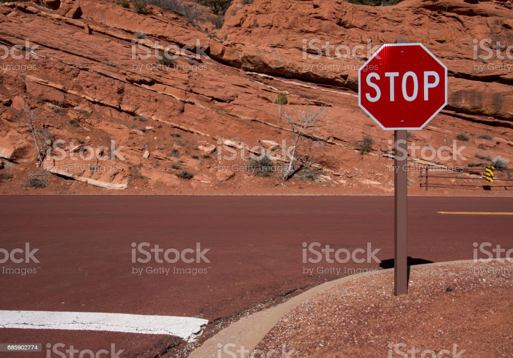 Stop Sign and Red Rock Wall stock photo