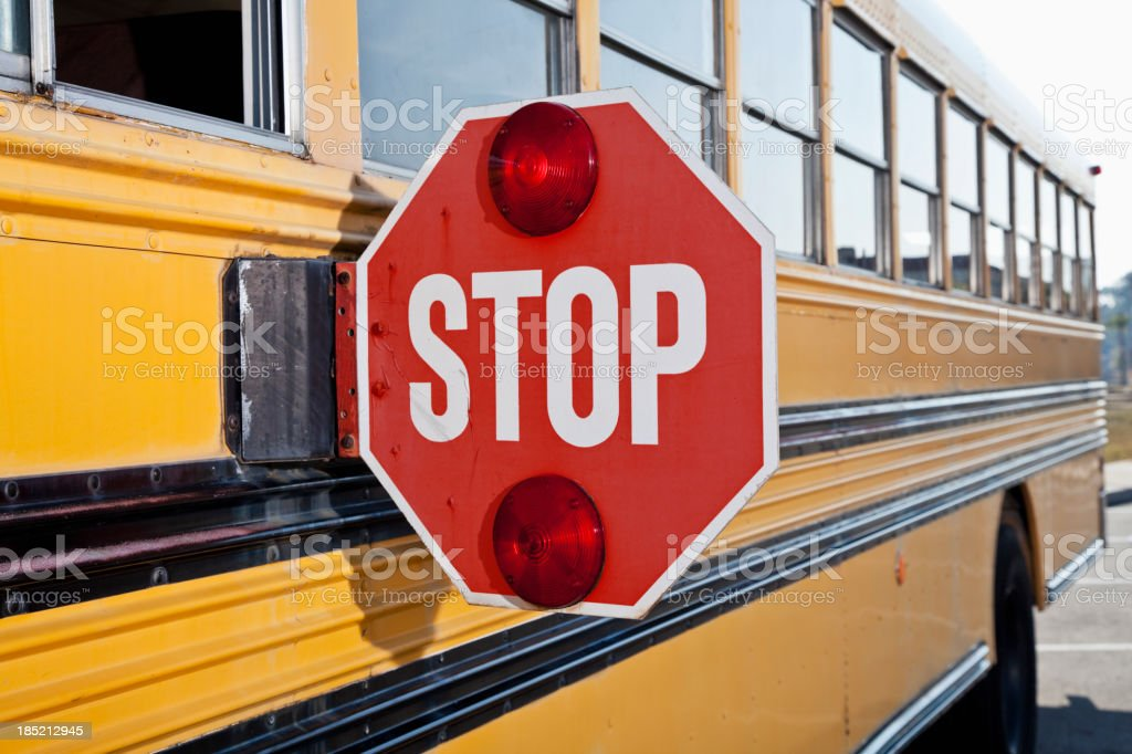 Stop sign on side of school bus stock photo