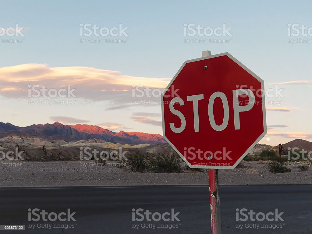 Stop Sign with Sunset Background over Desert Mountains stock photo