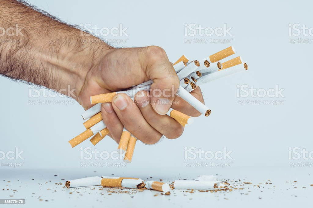 Man\'s hand crushing cigarettes. Stop smoking concept.