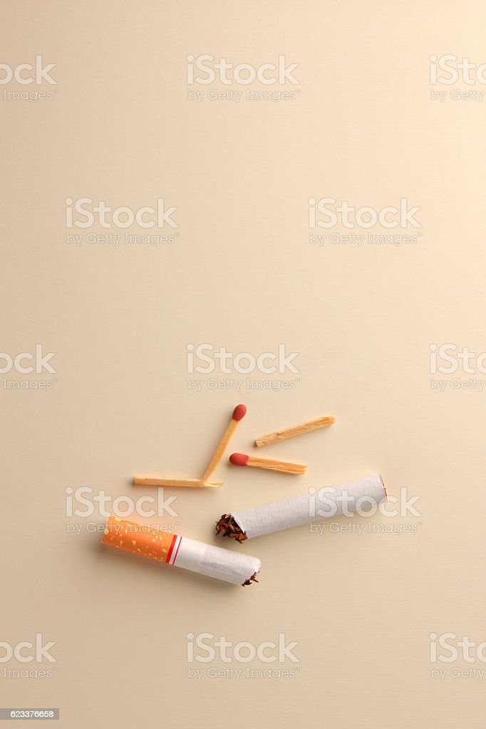 split cigarette and matchstick on paper background with space