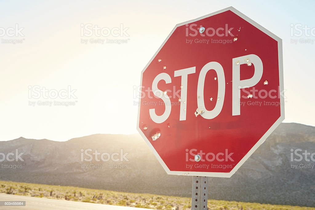 Stop Traffic Sign With Bullet Holes On Country Road stock photo