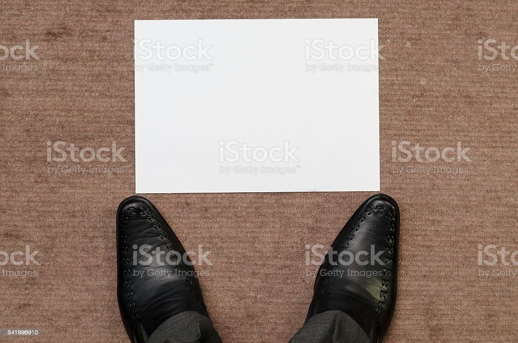 Stopping in front of blank paper on floor stock photo