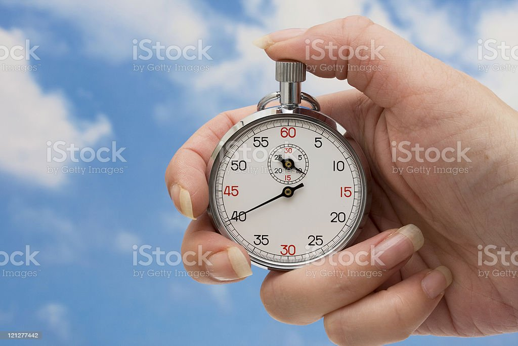 A stopwatch in someone's hand with the sky in the background royalty-free stock photo