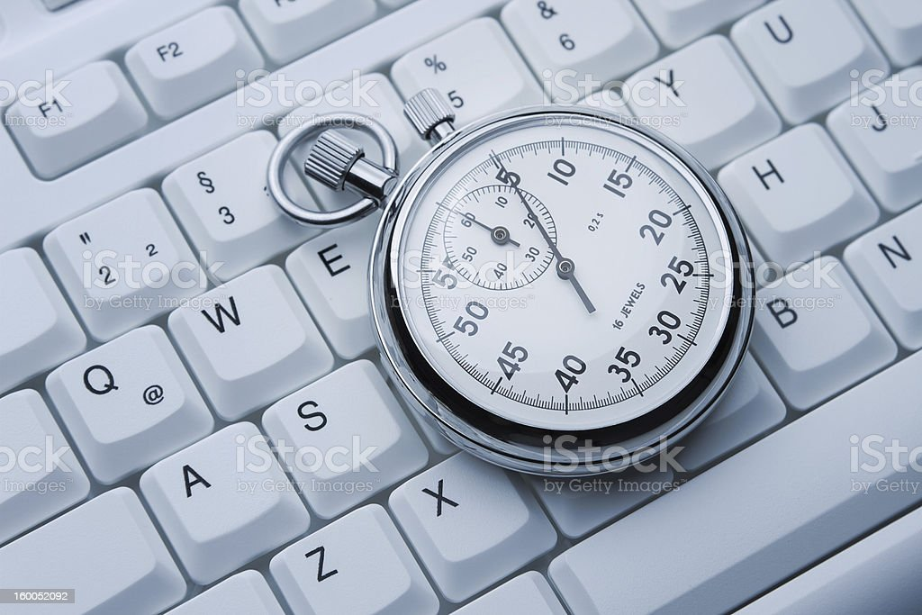 Stopwatch on white keyboard stock photo