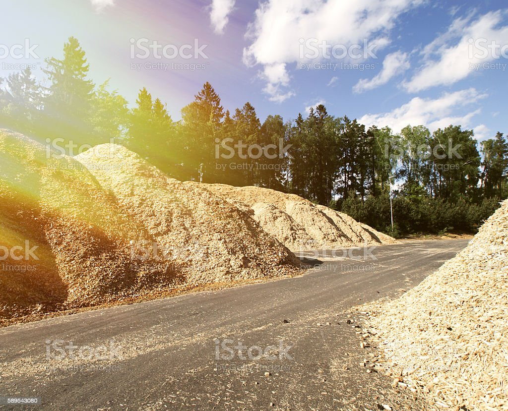 storage of wooden fuel against blue sky stock photo