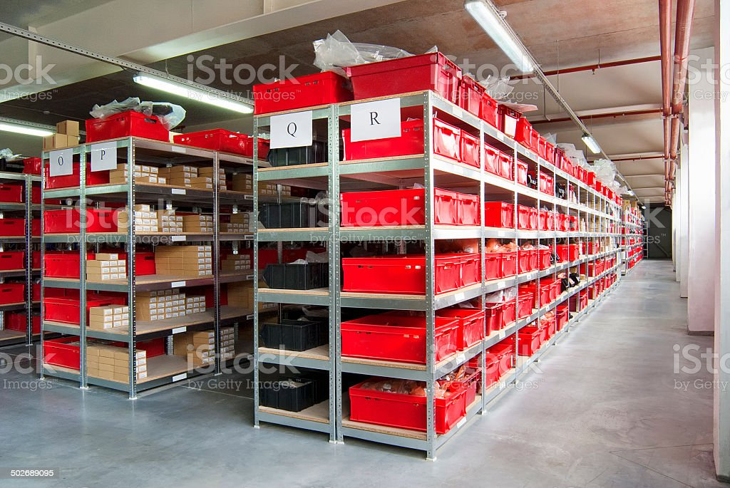 Storage room with red plastic drawers and shelves