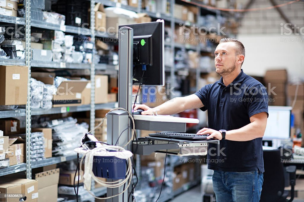 storage worker using computer stock photo