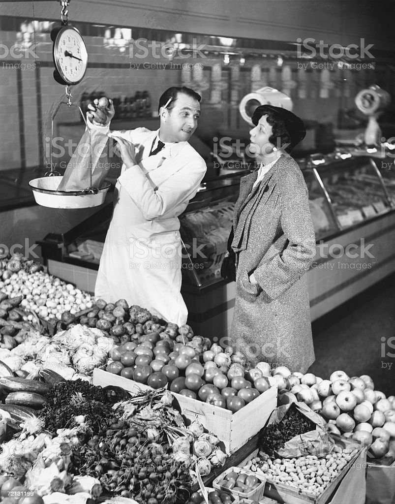 Store clerk weighing tomatoes for client (B&W) royalty-free stock photo