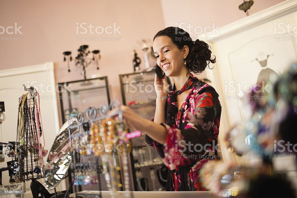 Store Owner Examining Accessories While On Call royalty-free stock photo