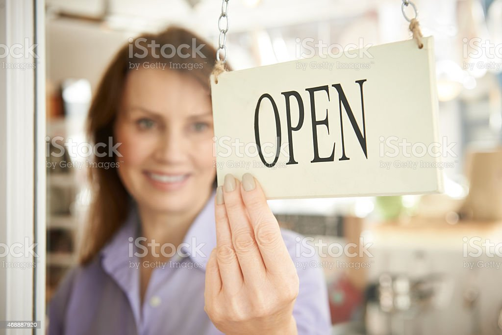 Store Owner Turning Open Sign In Shop Doorway stock photo