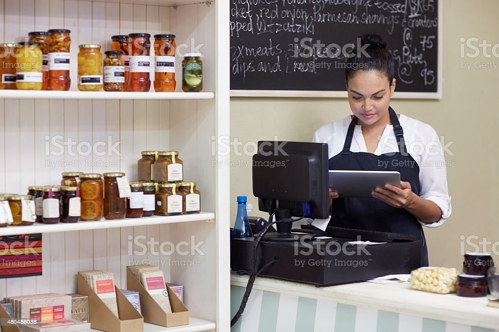Storing her store's admin in her tablet stock photo