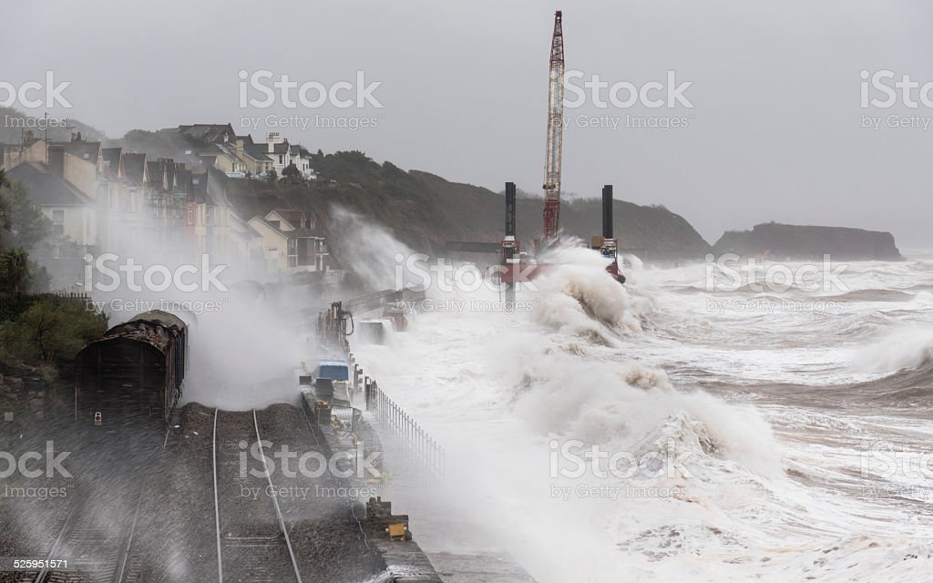 Storm at Dawlish with waves breaking over a goods train stock photo