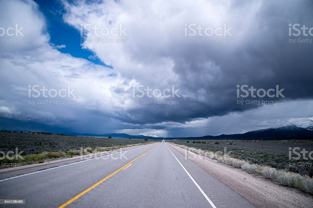 Storm clouds and endless staight road in Nevada stock photo