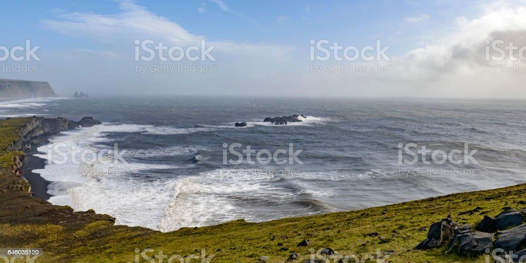 Storm clouds over Dyrholaey black basalt sand beach stock photo