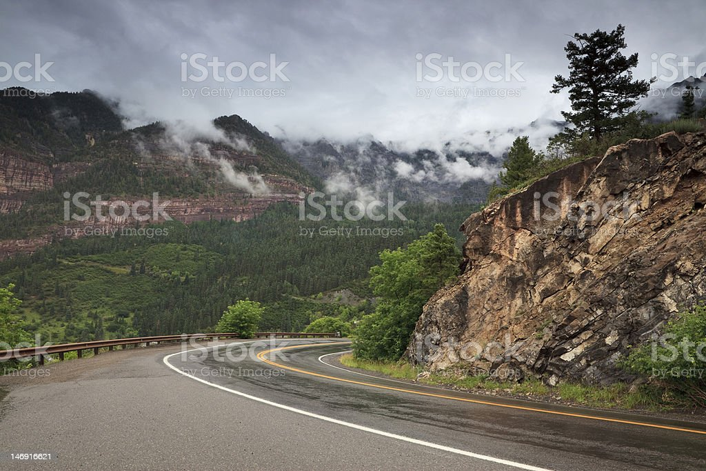 Storm clouds over mountain road in Colorado stock photo