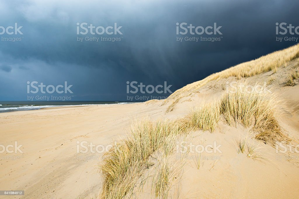Storm clouds over the beach with waves and sunlit dunes stock photo