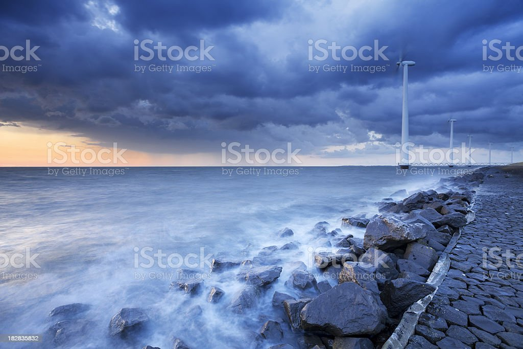 Storm clouds over wind turbines on a dike, The Netherlnads royalty-free stock photo