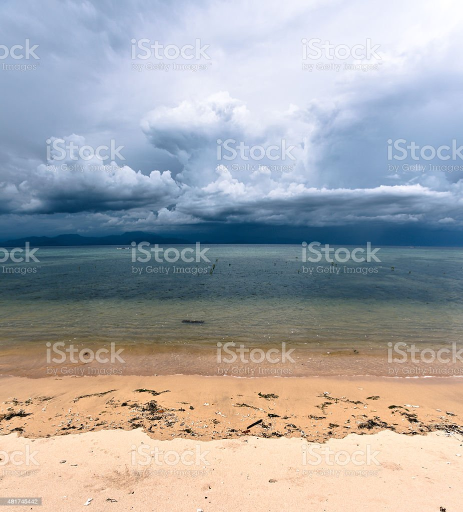 Storm clouds rising in tropical sand beach stock photo