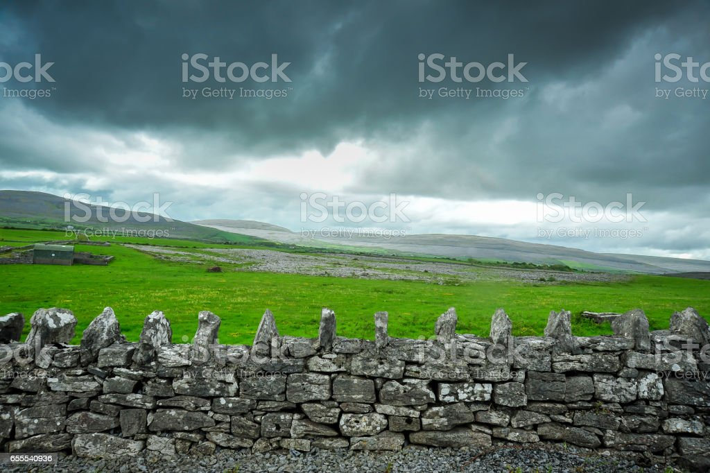Storm cloulds and old stone wall stock photo