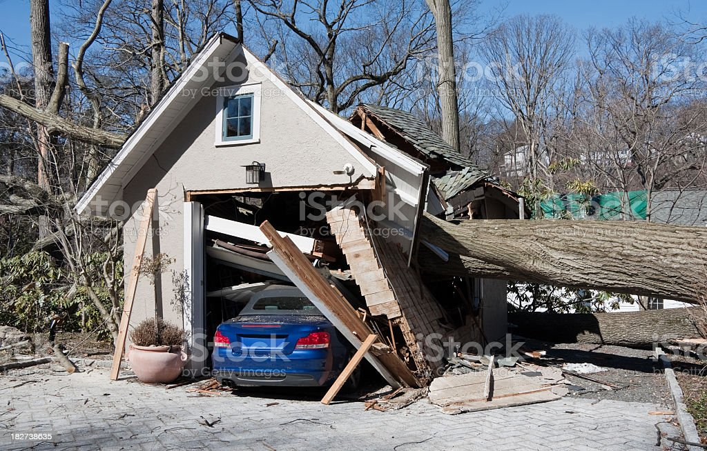 storm damage from tree onto a garage and car stock photo