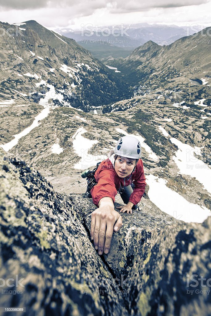 Storm looming behind a female rock climber in Colorado stock photo