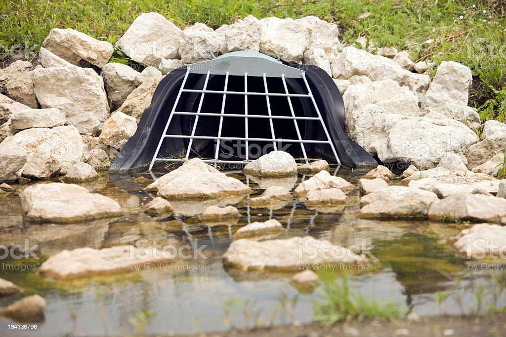 Storm Water Drain Culvert with Grate and Rocks royalty-free stock photo