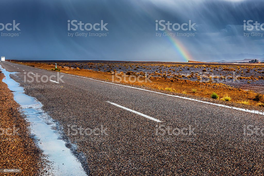 Storm with a rainbow above the road in the desert stock photo