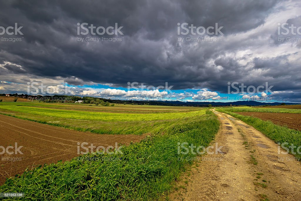 Stormy clouds above countryside road stock photo