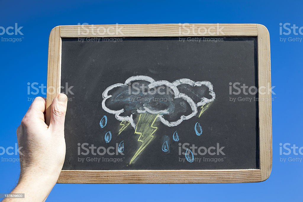 Stormy Clouds on Blackboard Against Blue Sky. Weather Concept stock photo