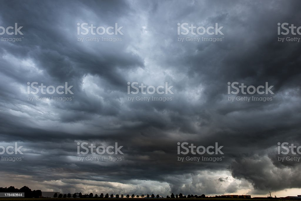 Sinister skyscape above tiny silhouette of treesPLEASE