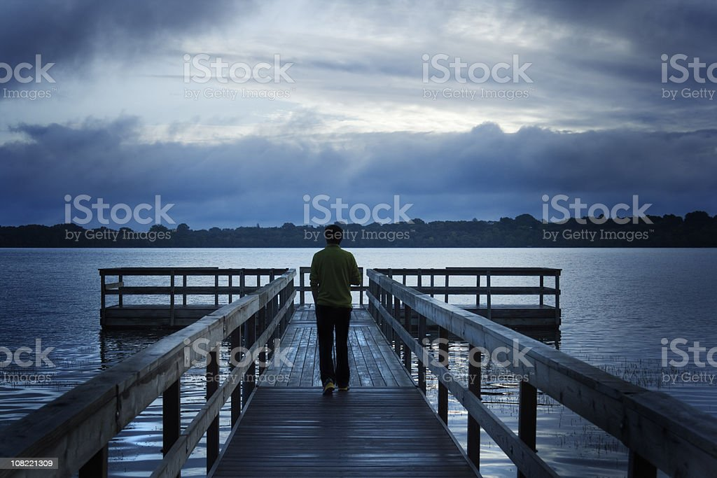 Stormy Morning with Man Walking on Wooden Dock over Lake royalty-free stock photo