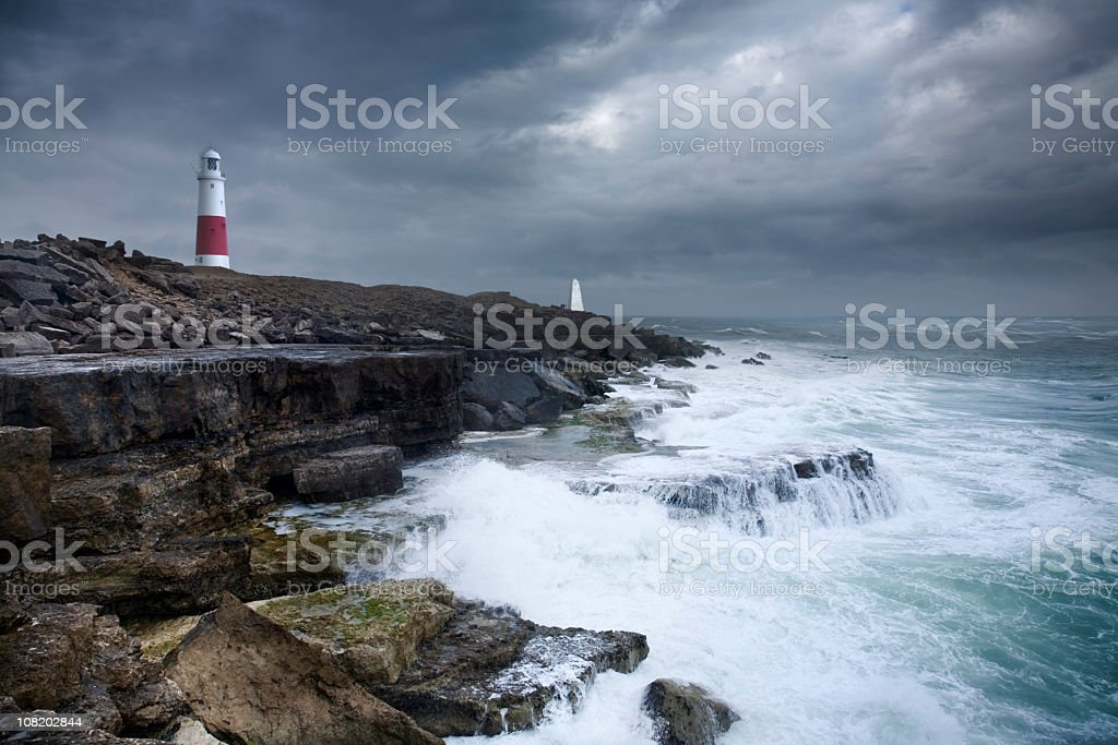 Stormy Sea and Sky on Rocky Coastline with Lighthouse royalty-free stock photo