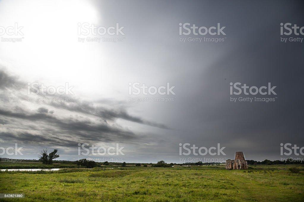 stormy skies over landmark St Benets Abbey Norfolk Broads England stock photo