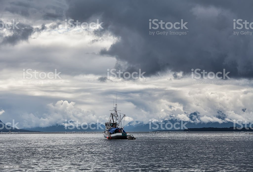 Stormy Skies with Fishing Boat stock photo