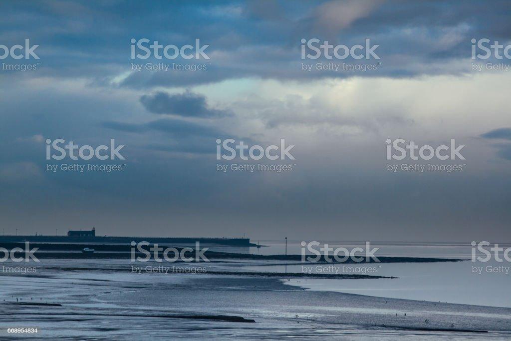 Stormy sky over stone jetty morecambe bay stock photo